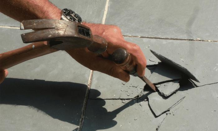 Процесс снятия старой плитки со стены